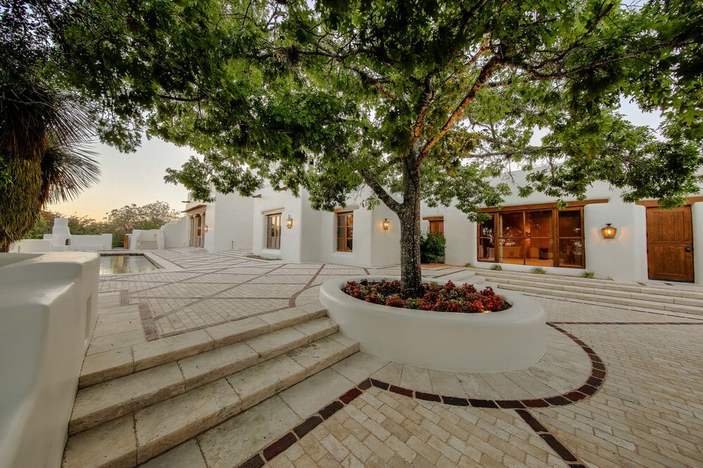 This is the area beyond the swimming pool area with a large planter with a tree and a view of the glass walls of the house on the far side. Image courtesy of Toptenrealestatedeals.com.