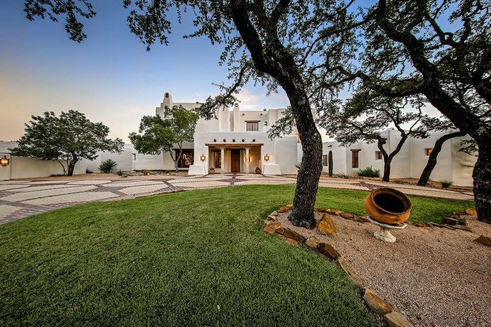 This is a a side of the house with a grass lawn and mature trees that complement the mosaic stone walkway. Image courtesy of Toptenrealestatedeals.com.