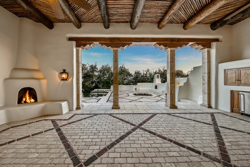 This is the covered patio with open walls and a couple of pillars leading to the poolside area with patterns and adobe structures. Image courtesy of Toptenrealestatedeals.com.