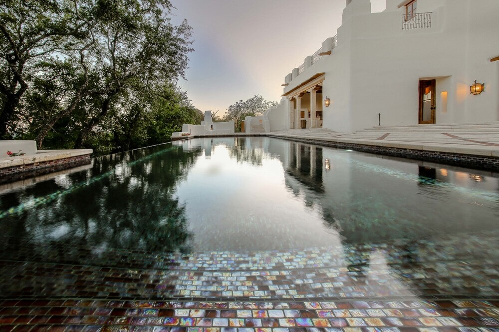 This is a close look at the infinity-edged swimming pool that brings color to the bright adobe walls of the house exterior. Image courtesy of Toptenrealestatedeals.com.