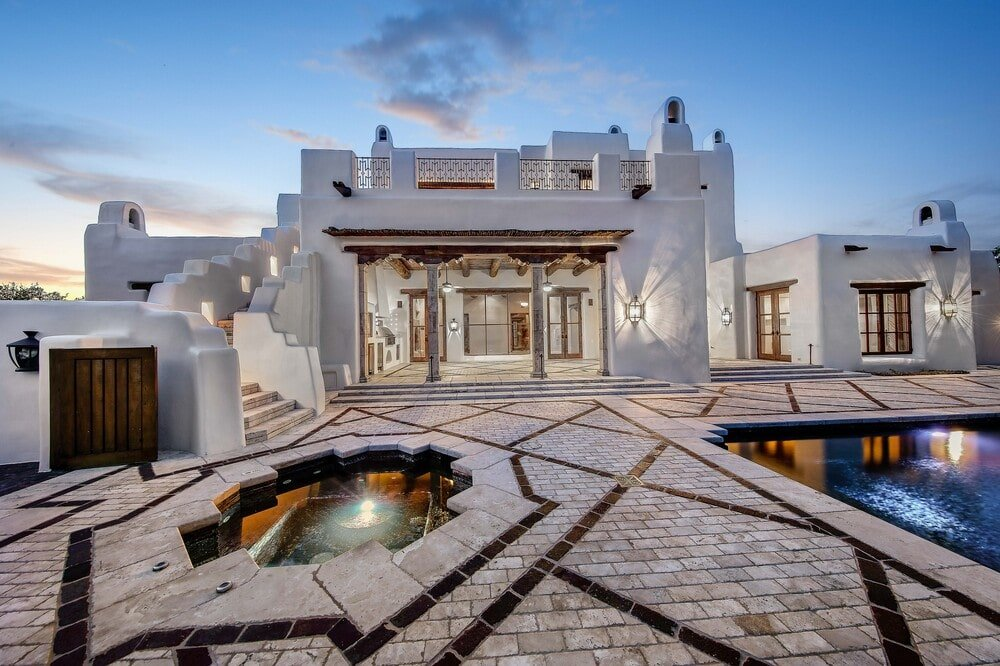 The poolside area just lies beyond the open walls of the covered patio. You can also see here the adobe structure that houses it with chimneys at the top. Image courtesy of Toptenrealestatedeals.com.