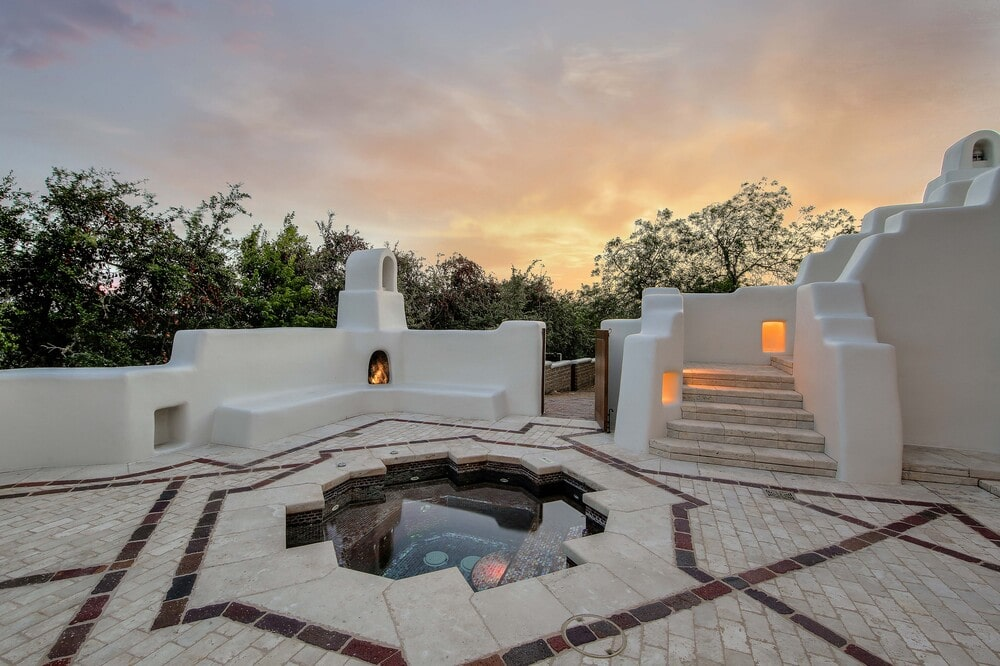 The poolside area has walkways of tiles with patterns and adobe structures complemented by the surrounding trees. Image courtesy of Toptenrealestatedeals.com.