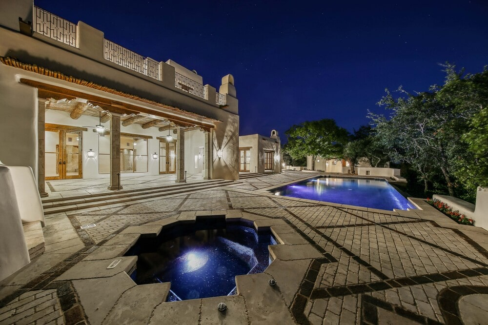 This is a nighttime view of the swimming pool area with that has lighting for the pool and spa. Image courtesy of Toptenrealestatedeals.com.