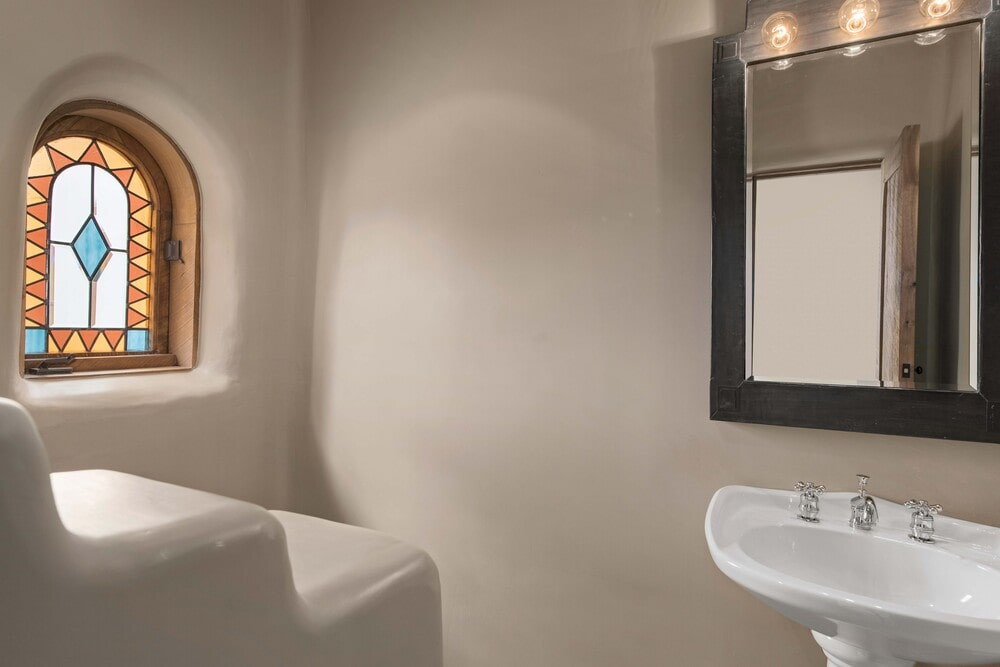 The powder room has adobe walls and a floating white porcelain sink topped with a wall-mounted mirror. Image courtesy of Toptenrealestatedeals.com.