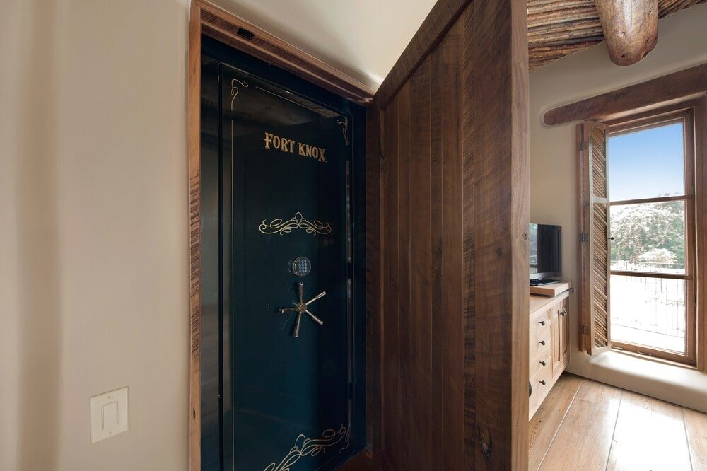 This is a close look at the large safe embedded into the wall of the house with a wooden cabinet door cover. Image courtesy of Toptenrealestatedeals.com.