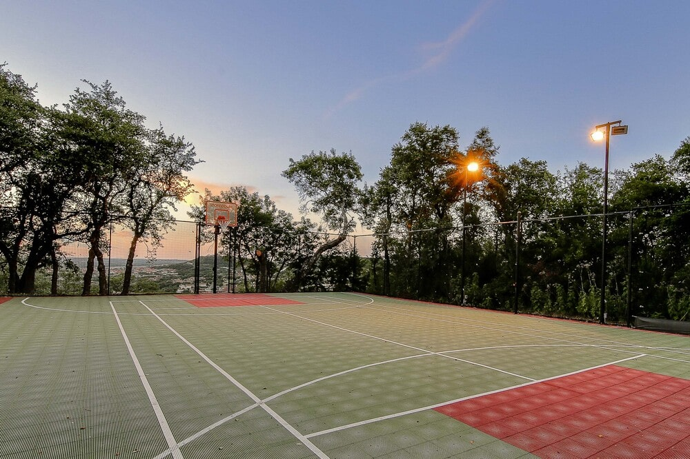 The property also has a tennis court with professional look to it surrounded by tall trees and lamp posts. Image courtesy of Toptenrealestatedeals.com.