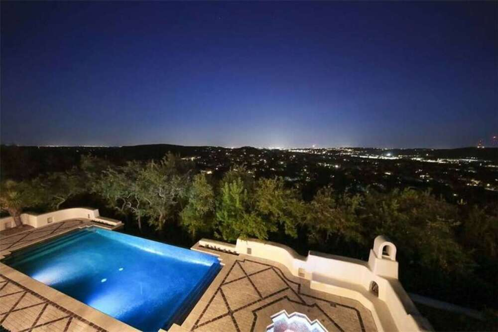 This is a look at the nighttime view of the balcony showcasing the ethereal glow of the swimming pool and the sweeping view of the city lights beyond the tall trees. Image courtesy of Toptenrealestatedeals.com.