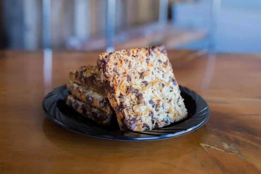 A plate of Hello Dolly Bars on a wooden table.
