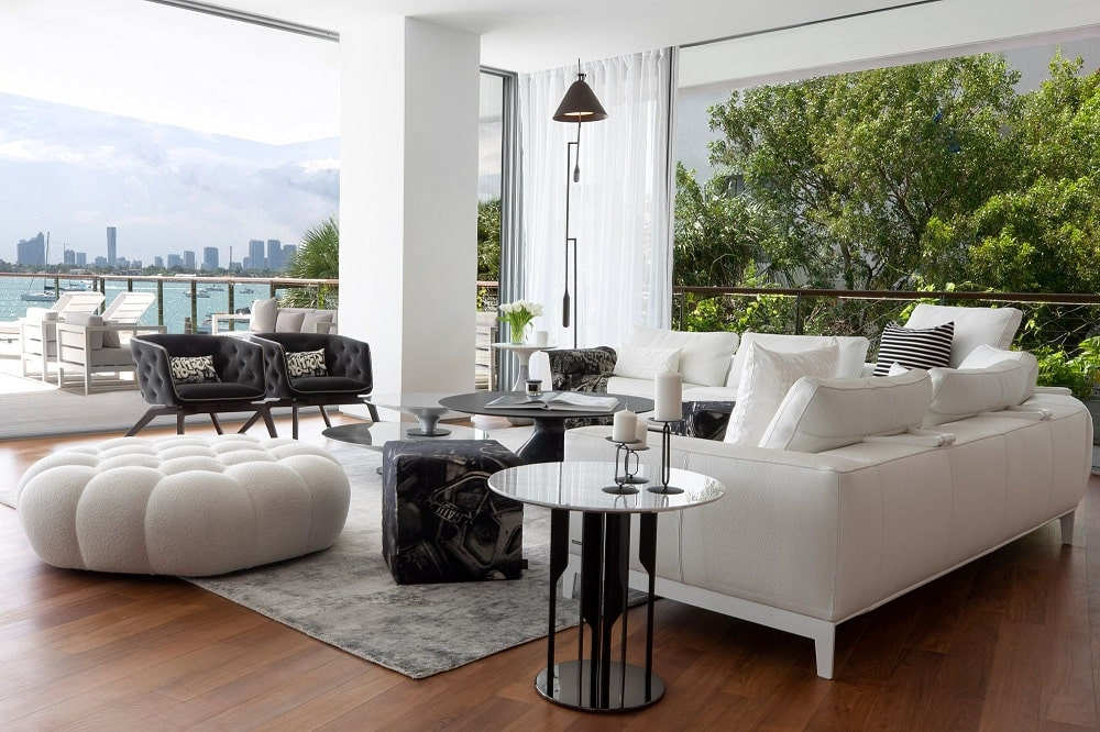 This is a close look at the living room that has bright beige sofas paired with end tables and matching dark coffee table, ottoman and armchairs.