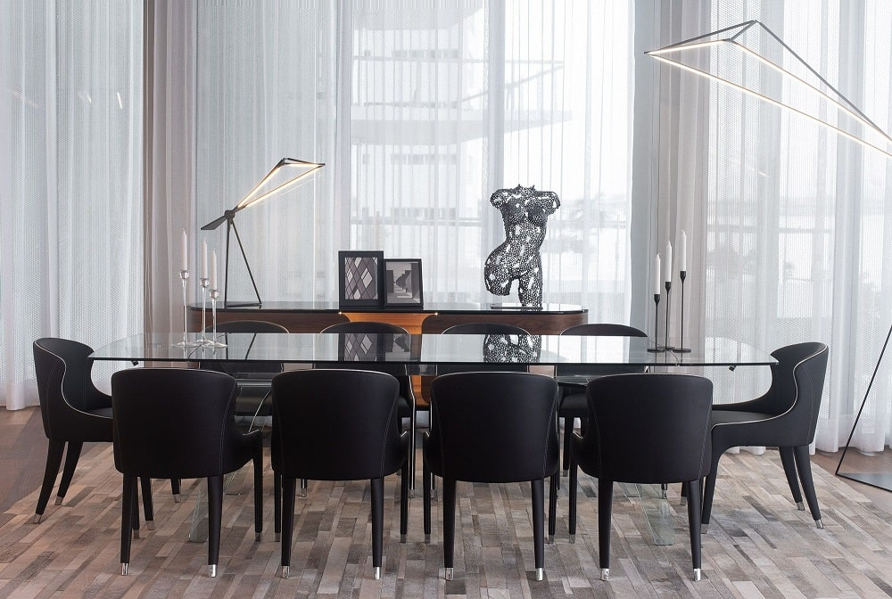 This is a closer look at the dining area that has a large glass-top dining table surrounded by black upholstered chairs.