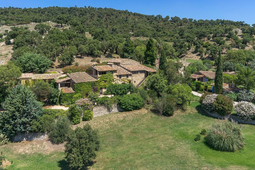 This is an aerial view of the property showcasing the earthy exteriors of the structures and the surrounding green tall trees. Image courtesy of Toptenrealestatedeals.com.