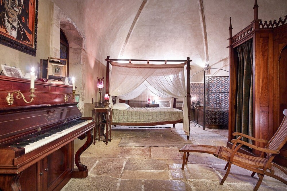 This is the bedroom with a tall dome ceiling over a large wooden four-poster bed with white curtains on a mosaic stone flooring. Image courtesy of Toptenrealestatedeals.com.