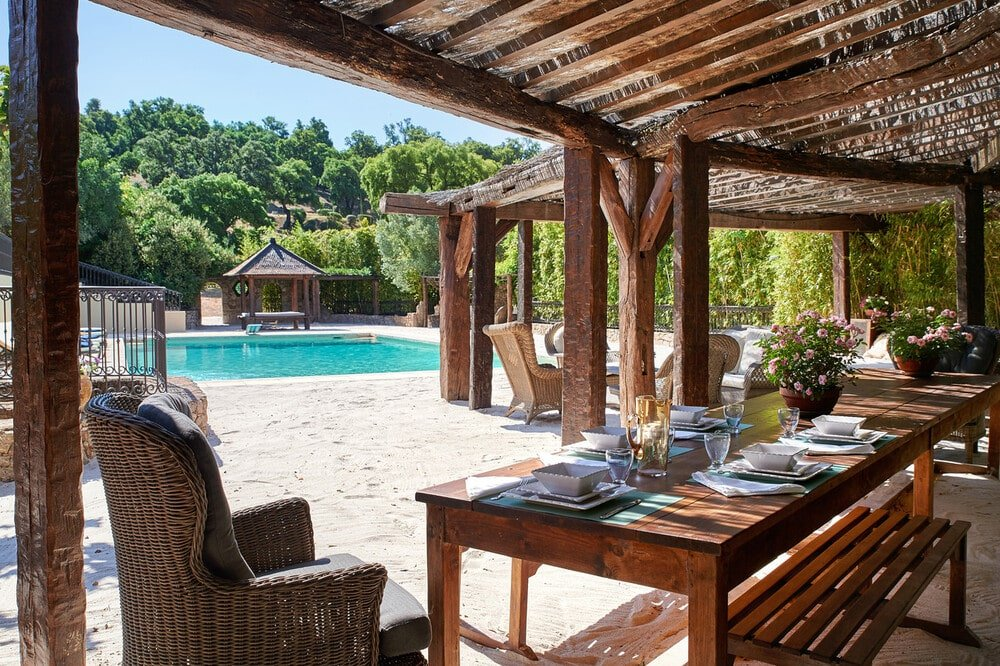 This is a daytime look at the wooden structures by the poolside area fitted with an outdoor dining area and a sitting area. Image courtesy of Toptenrealestatedeals.com.