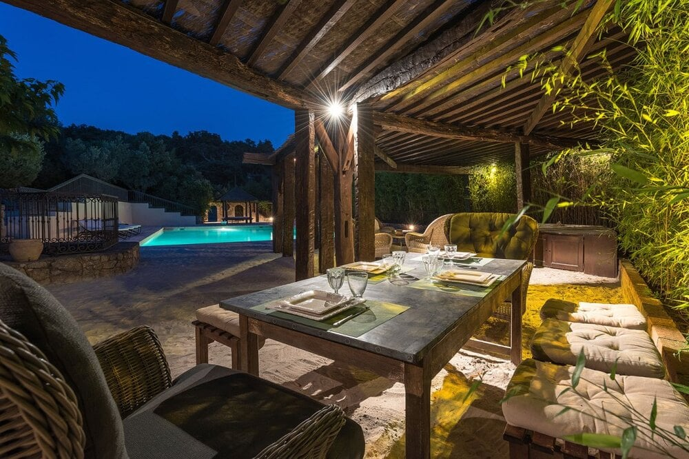 This is a nighttime view of the outdoor dining area by the swimming pool with large wooden structures a few steps from the pool area. Image courtesy of Toptenrealestatedeals.com.