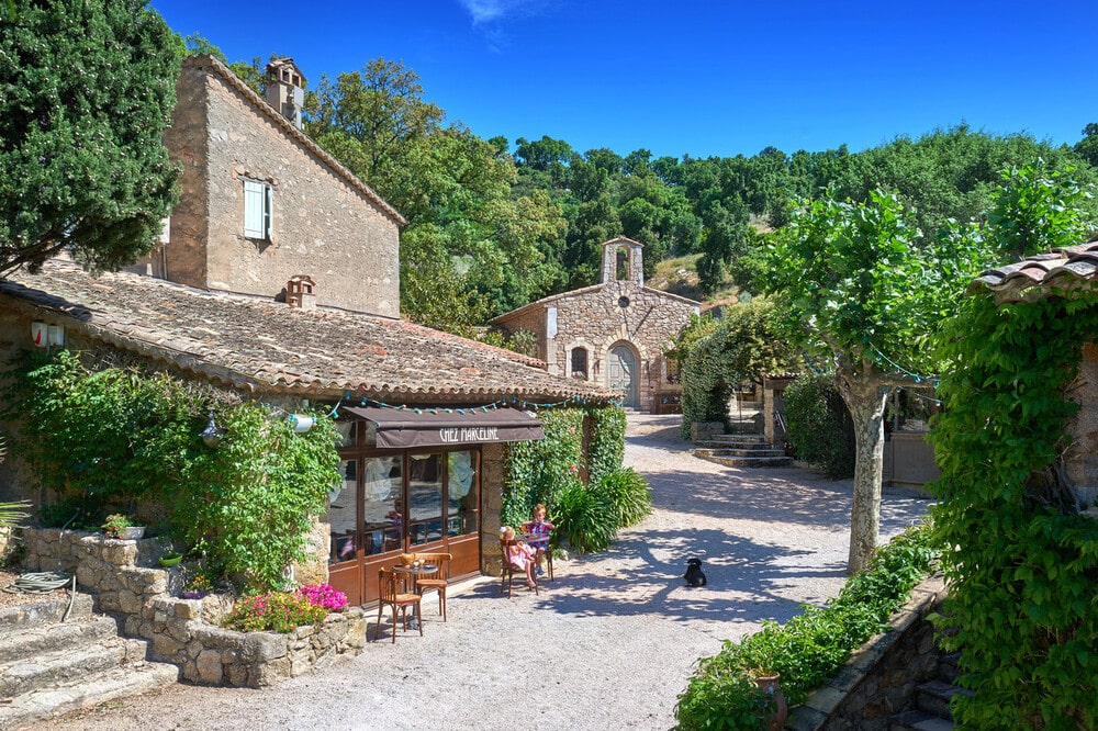 This is a daytime look at the structures of the French Provençal village showcasing the private restaurant and the guesthouse on the far side that used to be the village church. Image courtesy of Toptenrealestatedeals.com.