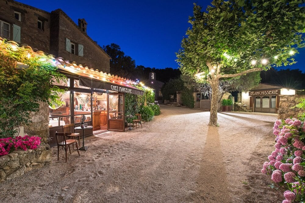 This is a nighttime view of the private restaurant in the property that has warm outdoor lighting and outdoor dining. Image courtesy of Toptenrealestatedeals.com.