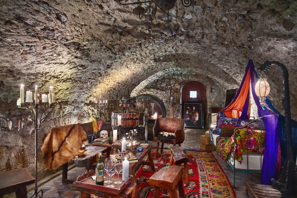 This is the wine cave with a textured stone cove ceiling and a wine tasting area with comfortable chairs and coffee tables. Image courtesy of Toptenrealestatedeals.com.