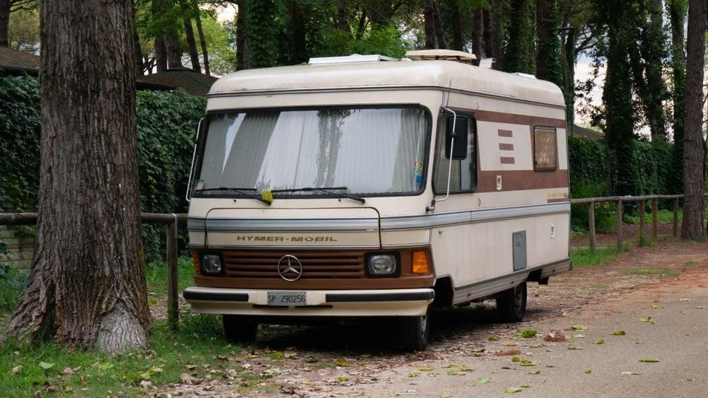 An old lightweight camper parked under a tree.