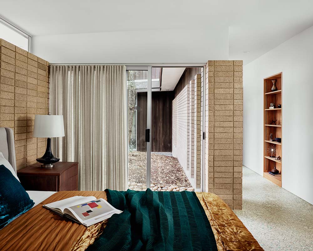 This is the primary bedroom with a large bed, white ceiling and walls accented with bricks.