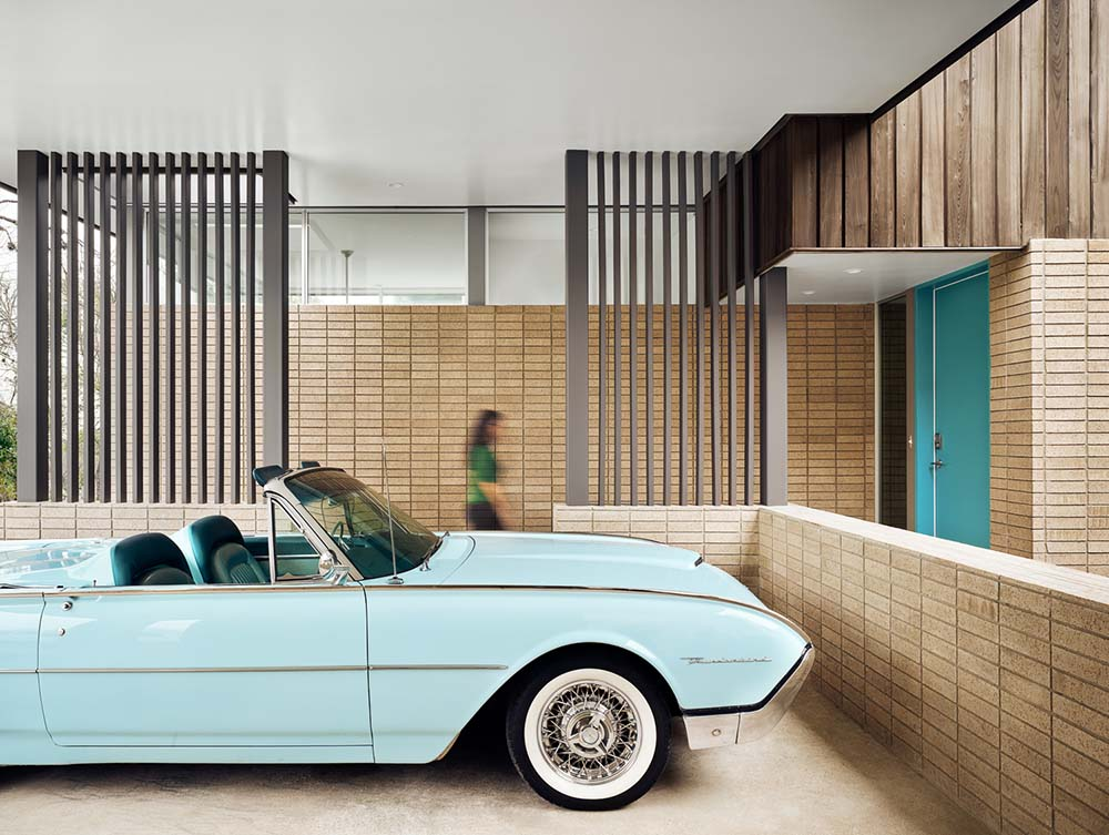 This is a look inside the car port with brick accents and slatted panels on the side.