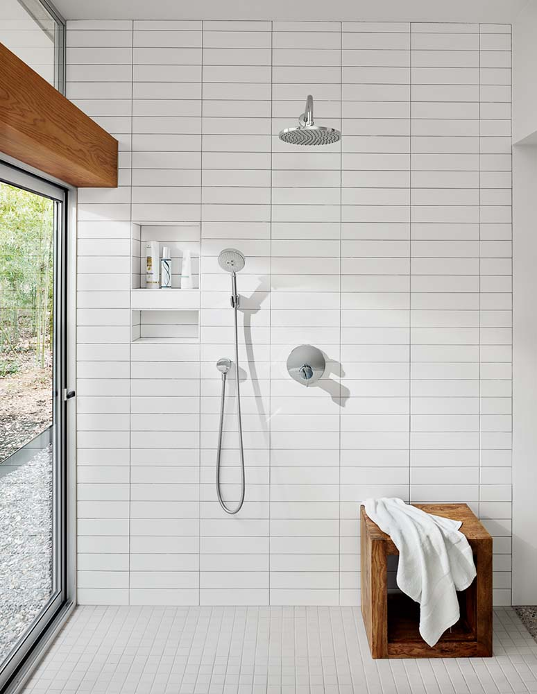 Across from the bathtub area is the open shower area with the same white subway tiles.