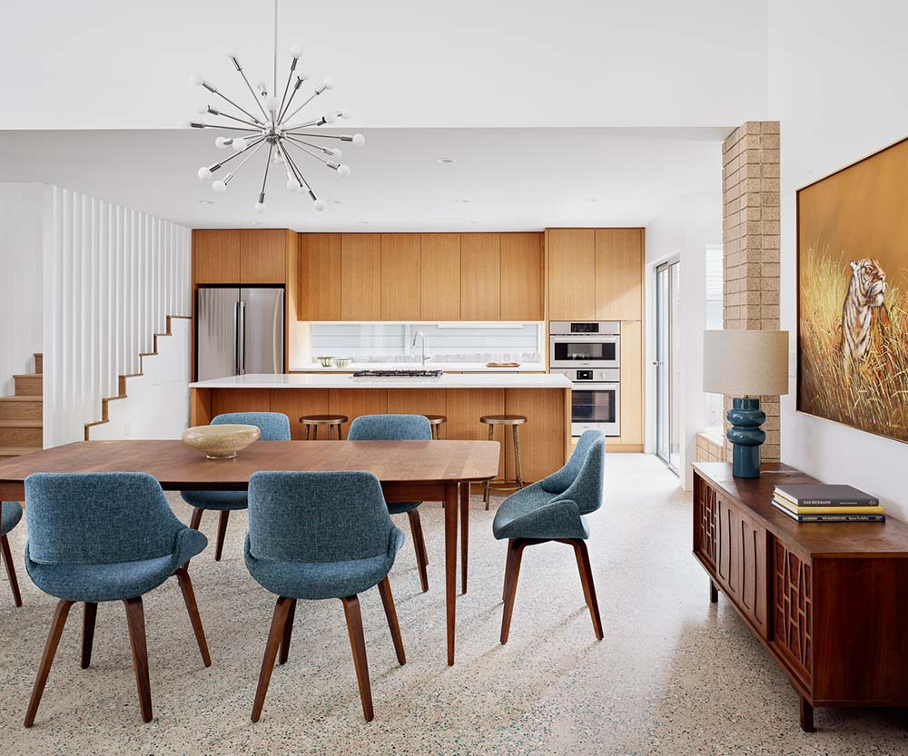 This is a look at the dining and kitchen areas with a wooden rectangular dining table surrounded by gray cushioned chairs.