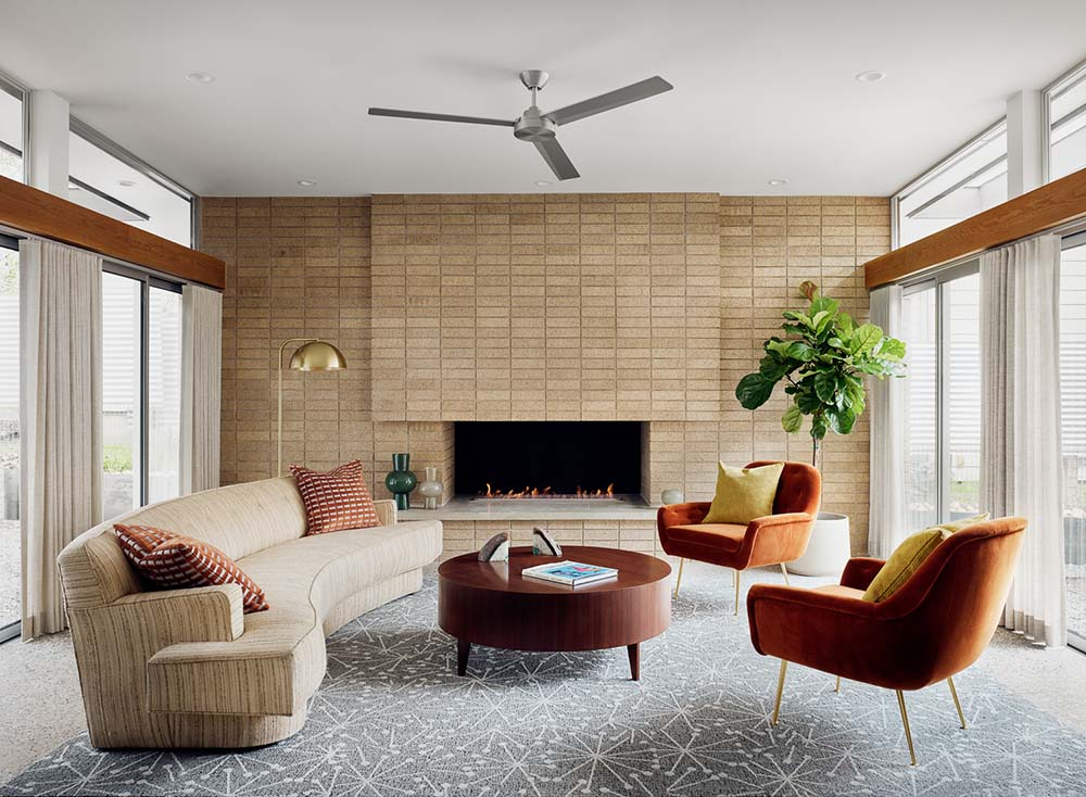 The living room has a large curved sofa and a round wooden coffee table across from the fireplace housed in a large brick wall.