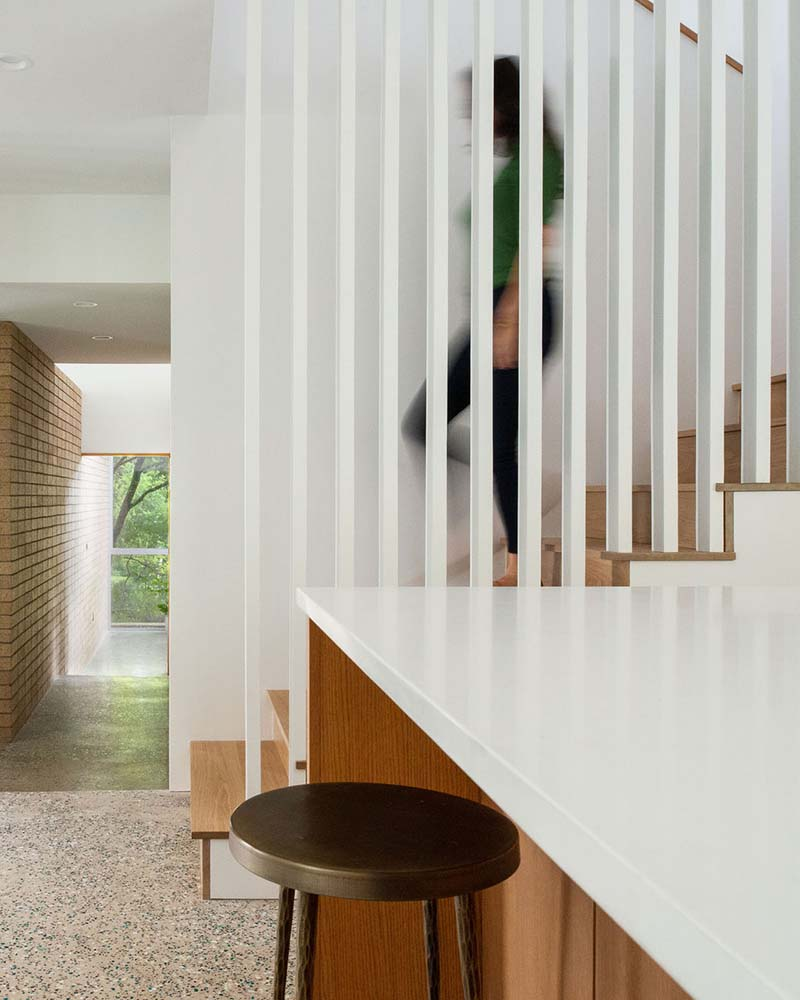 This is a close look at the staircase with white slatted railings on the side by the waterfall kitchen island.