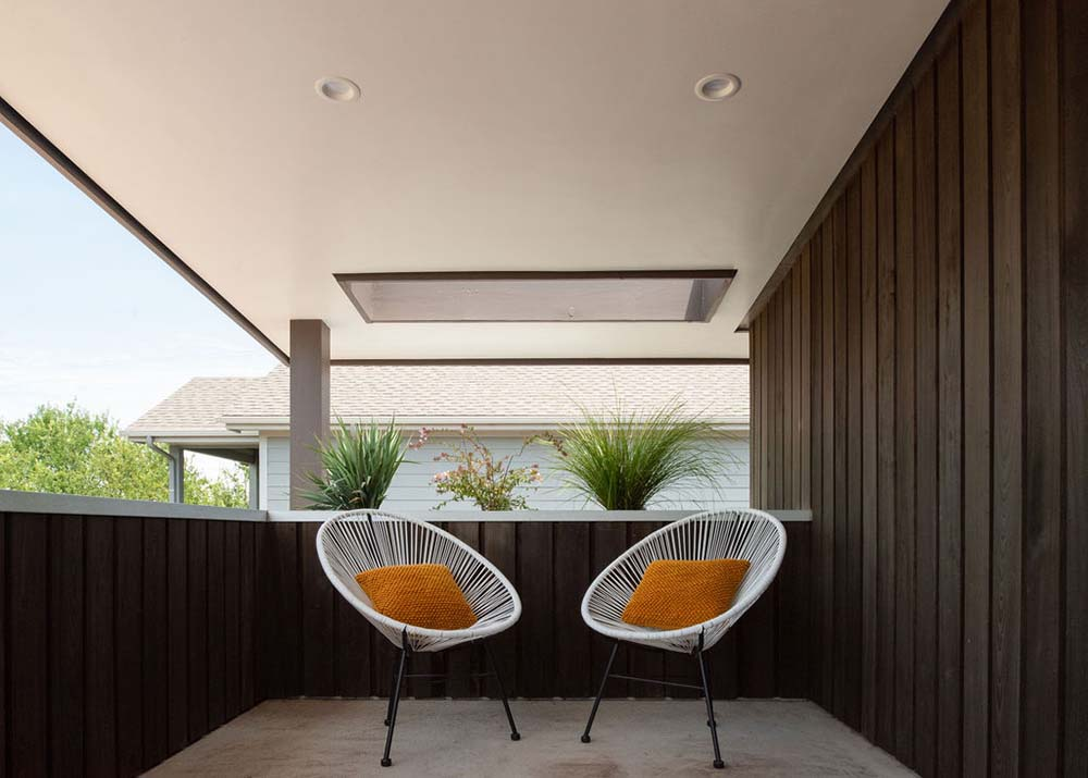 This is a close look at the balcony of the upper floor fitted with a couple of outdoor chairs.