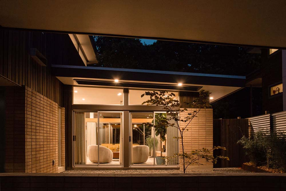 This is a view of the house landscape at night showcasing the warm lighting and glimpse of the interior through glass doors.