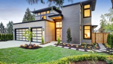This is the front of the house that has a Northwest-style landscaping of grass lawns, miniature gardens and a concrete walkway leading to the back of the house with a wooden gate.