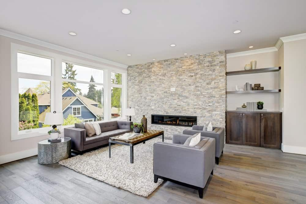 This is a close look at a Northwest-style living room with a large stone wall that houses the modern fireplace across from the sofas set.