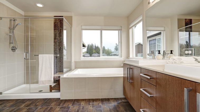 This is a Northwest-style primary bathroom with a bathtub under the window attched to the glass-enclosed shower area and the vanity that has wooden cabinets and drawers.