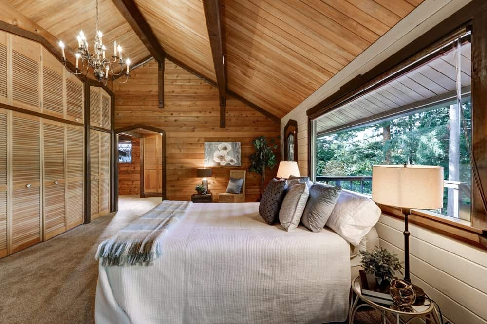 This is a Northwest-style primary bedroom with a spacious area, arched wooden ceiling, large windows and a bright bed topped with a chandelier.