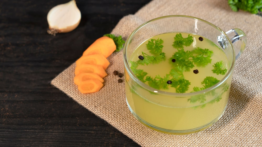 A glass of chicken bone broth with carrot, onion, parsley, and peppercorn.