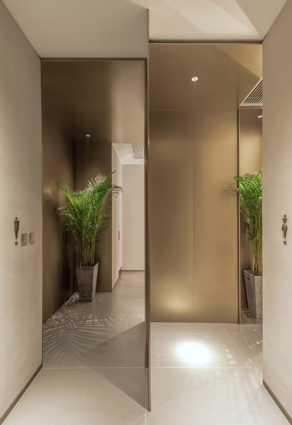 This is a close look at the entryways for the male and female comfort rooms adorned with potted plants.