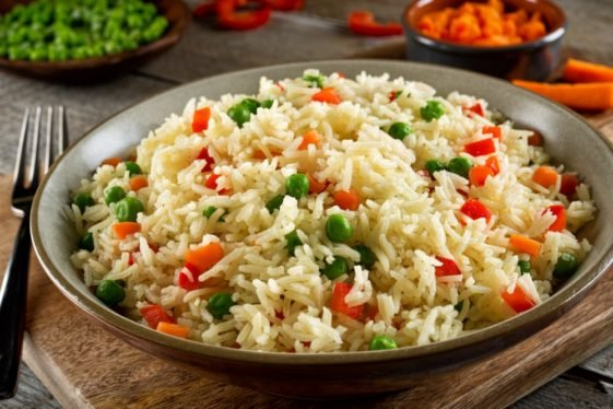 A plate of rice pilaf with peas and carrots.