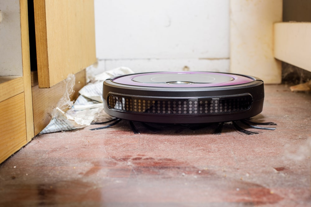 Robotic vacuum cleaner on a dirty floor.