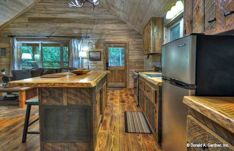 Kitchen with a two-door fridge, a breakfast island, and wooden cabinetry that blends in with the floor and walls.