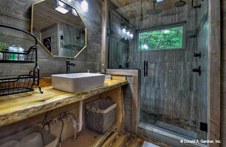 The primary bathroom offers a walk-in shower and a wooden vanity paired with an octagonal mirror.