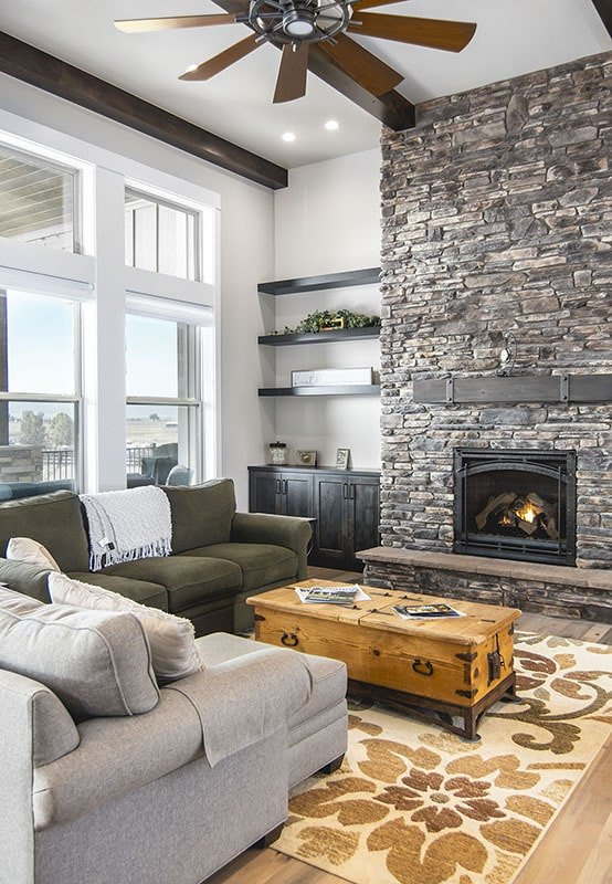 The living room has clerestory windows, a stone fireplace, and comfy sectionals paired with a wooden chest coffee table.