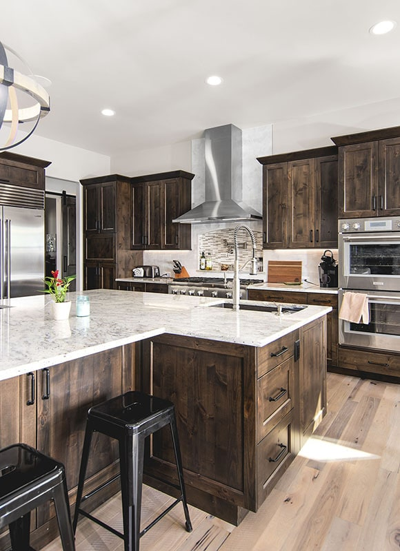 The kitchen is equipped with marble countertops, stainless steel appliances, wooden cabinetry, and a sink fitted on the island.