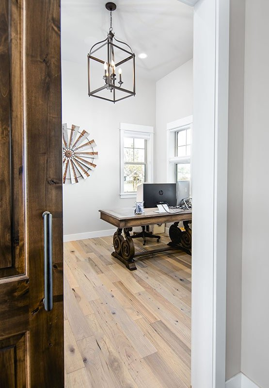 Home office with a large caged pendant, a wooden desk, and around artwork adorning the stark white walls.