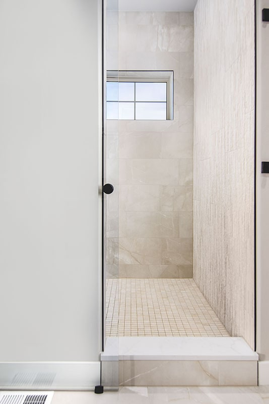 Walk-in shower with tiled walls, a glass hinged door, and a window that lets natural light in.