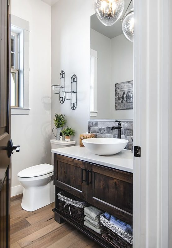 The powder room offers a toilet and a dark wood vanity with a vessel sink, an iron faucet, and a frameless mirror.