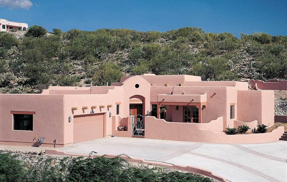 This is a classic adobe style home with an earthy tone to its exterior walls that stands out against the background and the large driveway.