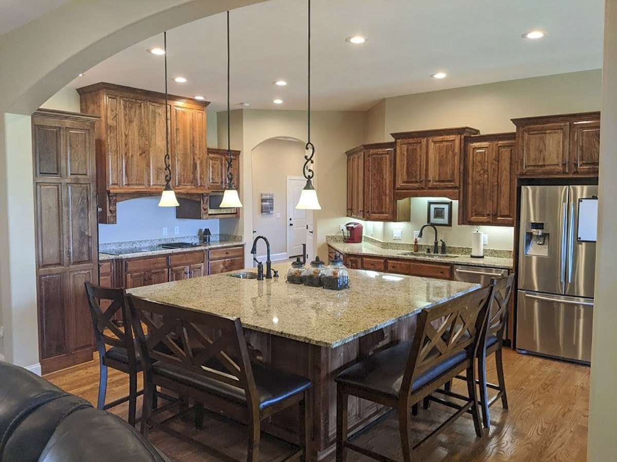 The kitchen offers natural wood cabinetry, stainless steel appliances, an immense center island.
