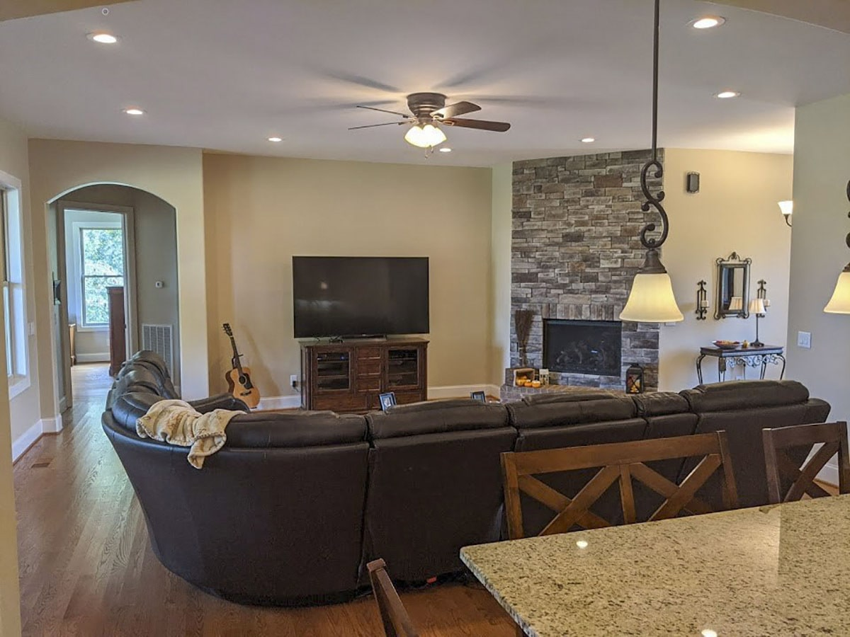 The living room includes a leather sectional, a TV, and a corner fireplace.