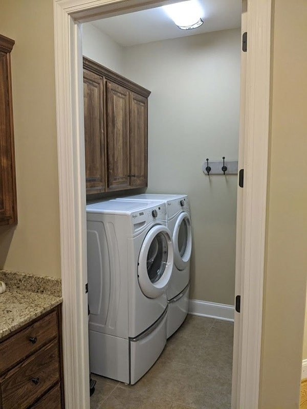 Smaller laundry room with white front load appliances and overhang cabinets.