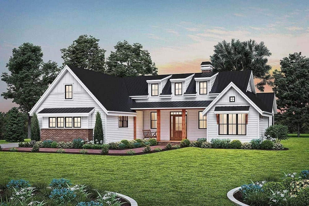 This is a front look at the American farmhouse-style home with a brick walkway leading to a covered entrance topped with three modern dormer windows.